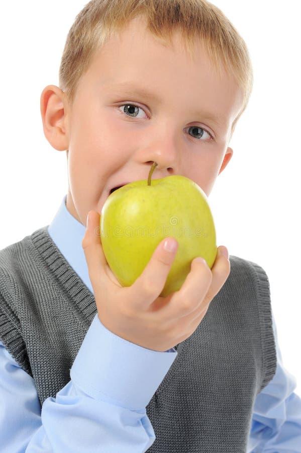 De jongen eet een appel stock foto
