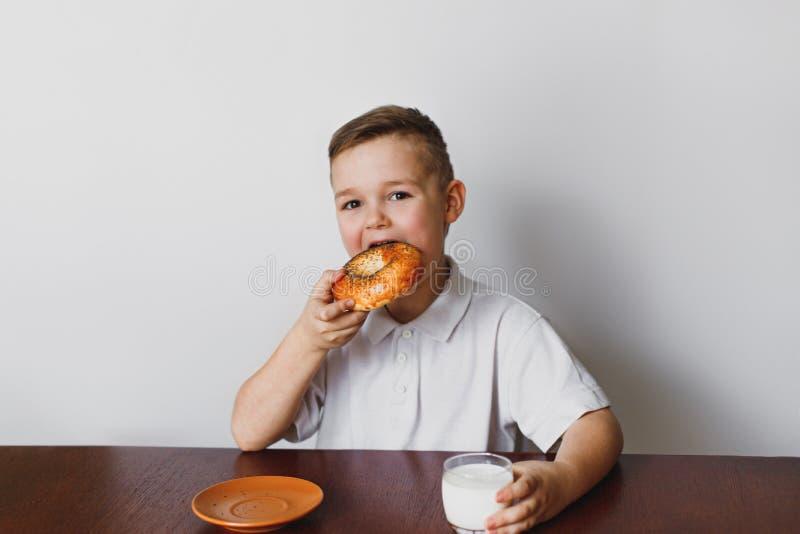 De jongen eet een ongezuurd broodje en drinkt melk stock foto