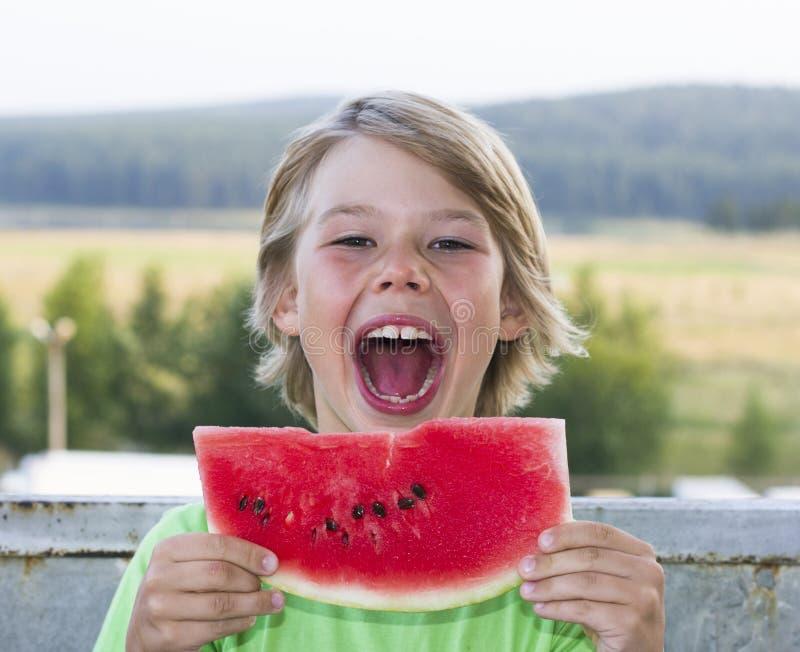 De jongen eet een stuk van watermeloen stock foto