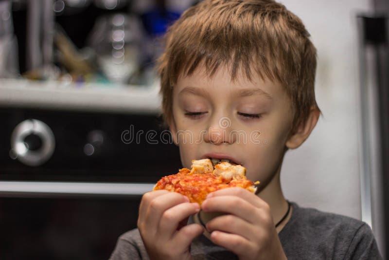 De jongen eet een zeer smakelijke pizza met groot genoegen stock afbeelding