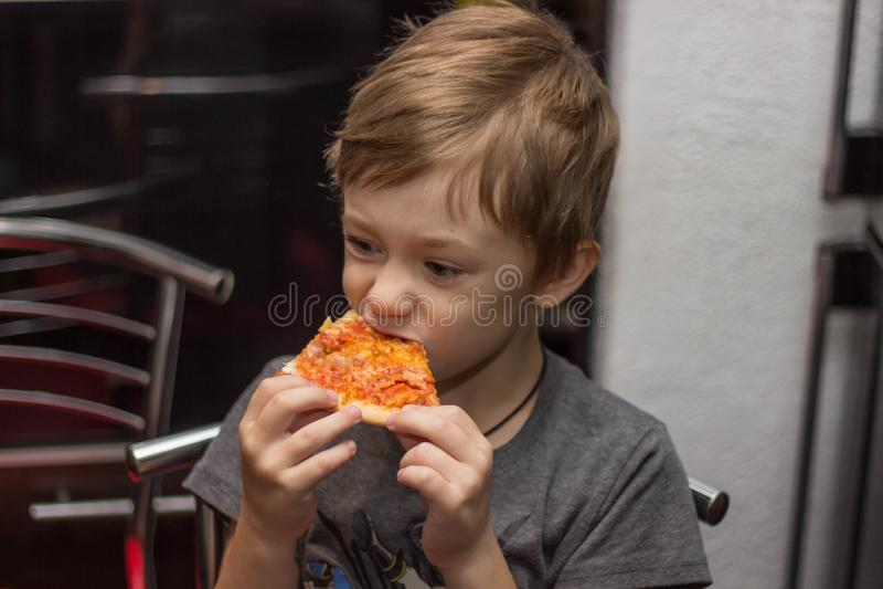 De jongen eet een zeer smakelijke pizza met groot genoegen royalty-vrije stock fotografie