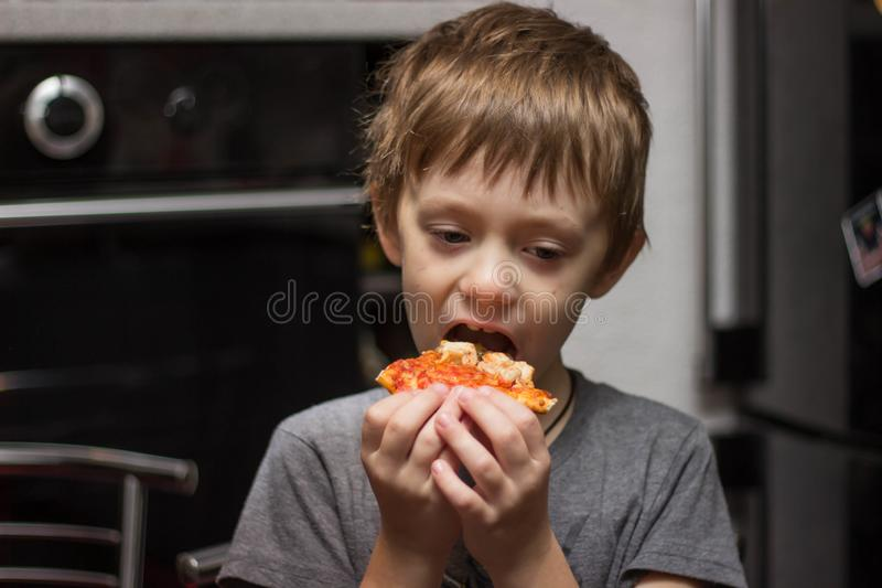 De jongen eet een zeer smakelijke pizza met groot genoegen royalty-vrije stock afbeelding