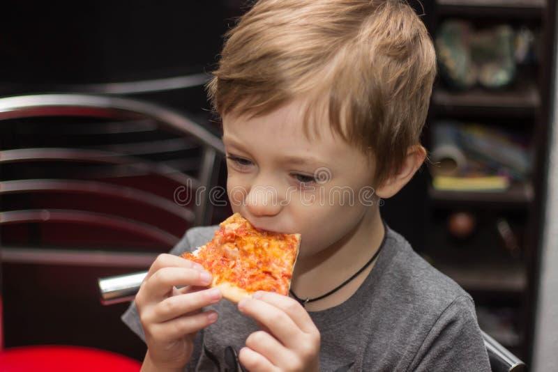 De jongen eet een zeer smakelijke pizza met groot genoegen stock afbeeldingen