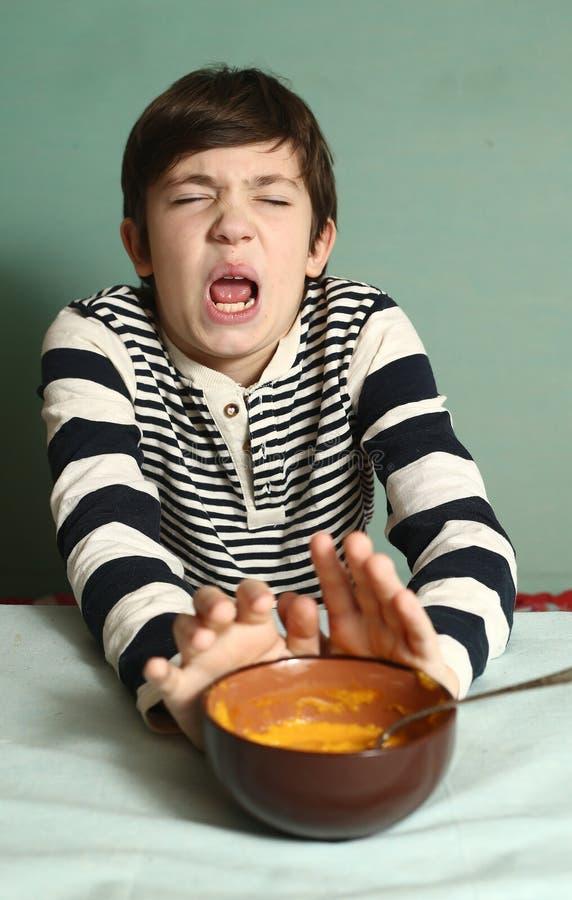 De jongen eet pompoensoep met uitdrukking van afschuw royalty-vrije stock foto's