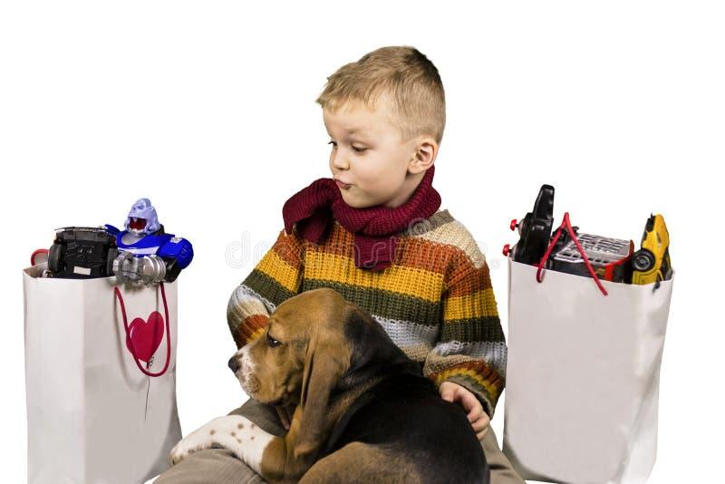De jongen en de hond overwegen giften stock foto