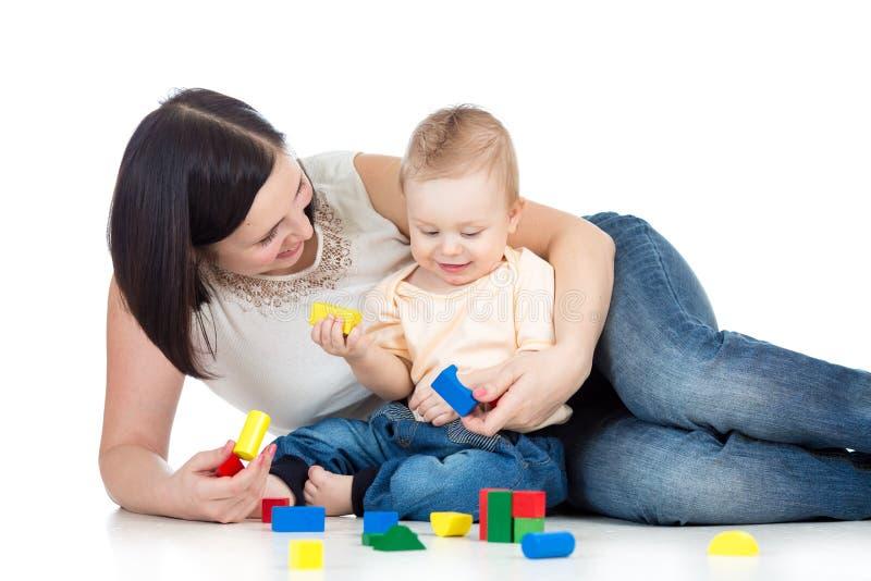 De jongen en de moeder het spelen van het kind samen met bouw vastgesteld stuk speelgoed royalty-vrije stock afbeelding