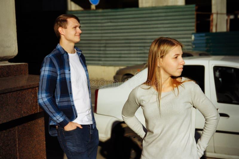 De jongen en het meisje bevinden zich op de ontevreden straat, ruzie, het scheiden Spanning op het werk royalty-vrije stock afbeeldingen