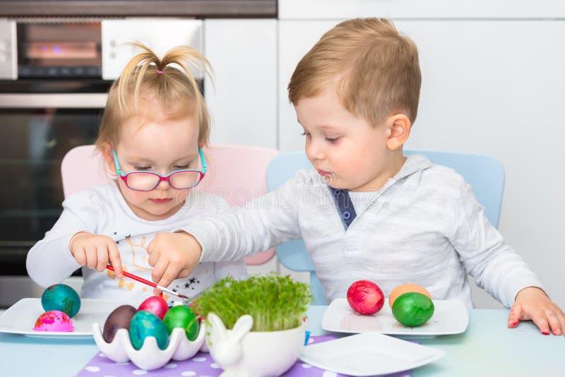 De jongen en het meisje brengen het schilderen eieren voor Pasen samen stock afbeelding