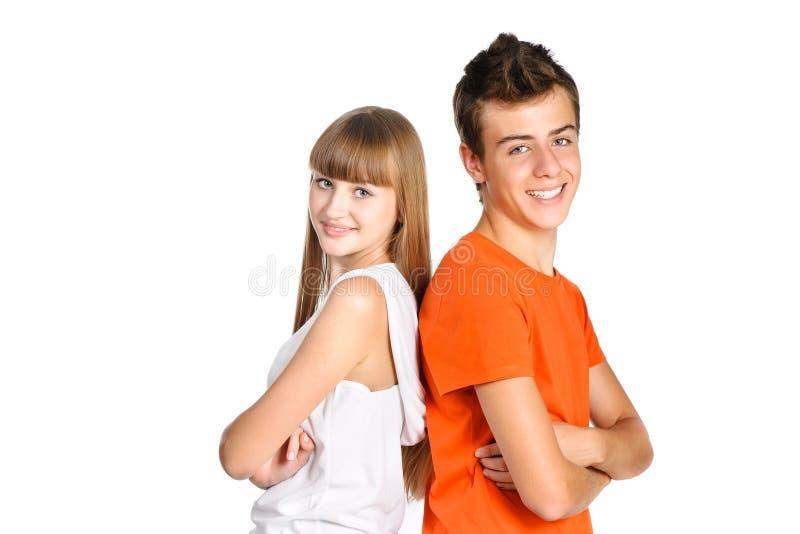 De jongen en het meisje die van de tiener over wit glimlachen stock afbeeldingen