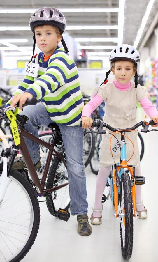 De jongen en het meisje in helmen zitten op fietsen stock afbeelding