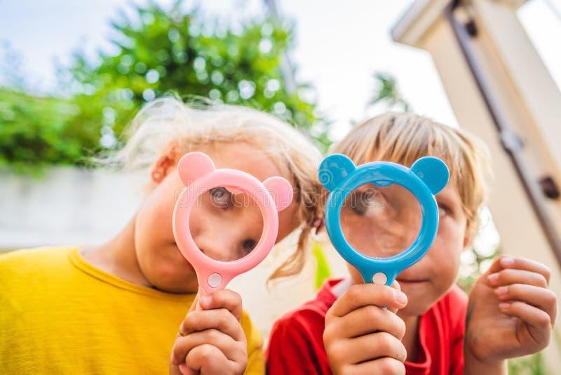 De jongen en het meisje kijken in een vergrootglas tegen de achtergrond van de tuin Huis het scholen royalty-vrije stock foto