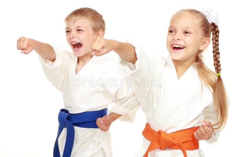 De jongen en het meisje in kimono slaan hand royalty-vrije stock foto's