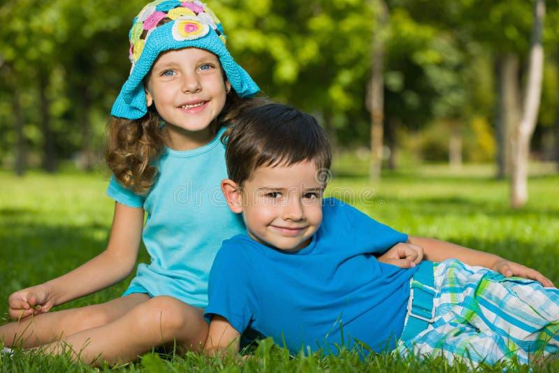 De jongen en het meisje rusten in het park royalty-vrije stock afbeeldingen