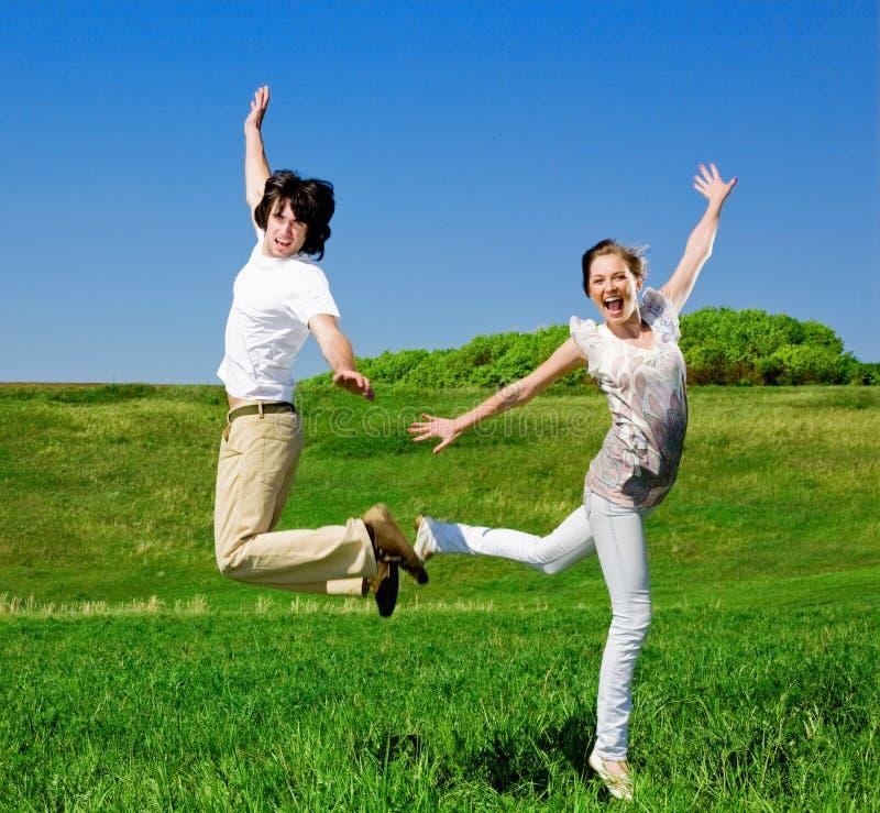 De jongen en het meisje springen stock fotografie