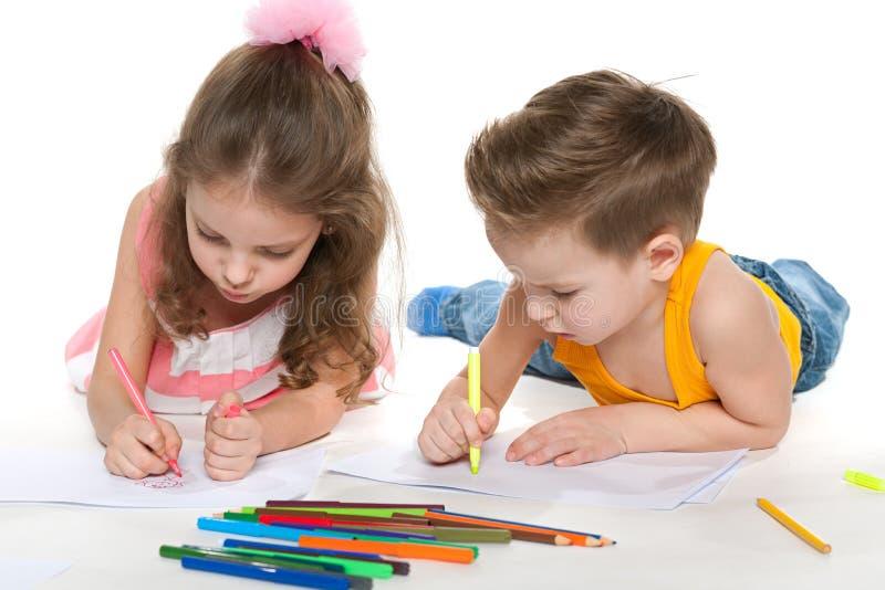 De jongen en het meisje trekken op papier royalty-vrije stock foto