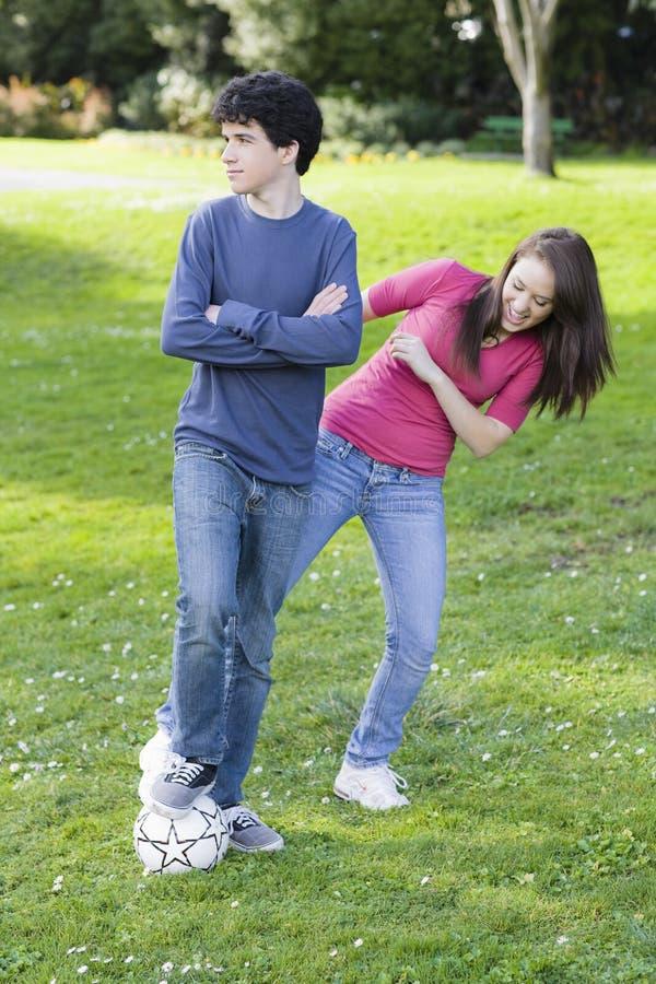 De Jongen en het Meisje van de tiener met de bal van het Voetbal stock afbeeldingen