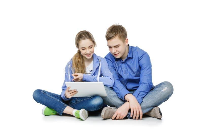 De jongen en het meisje van de tienerleeftijd met tablet stock fotografie