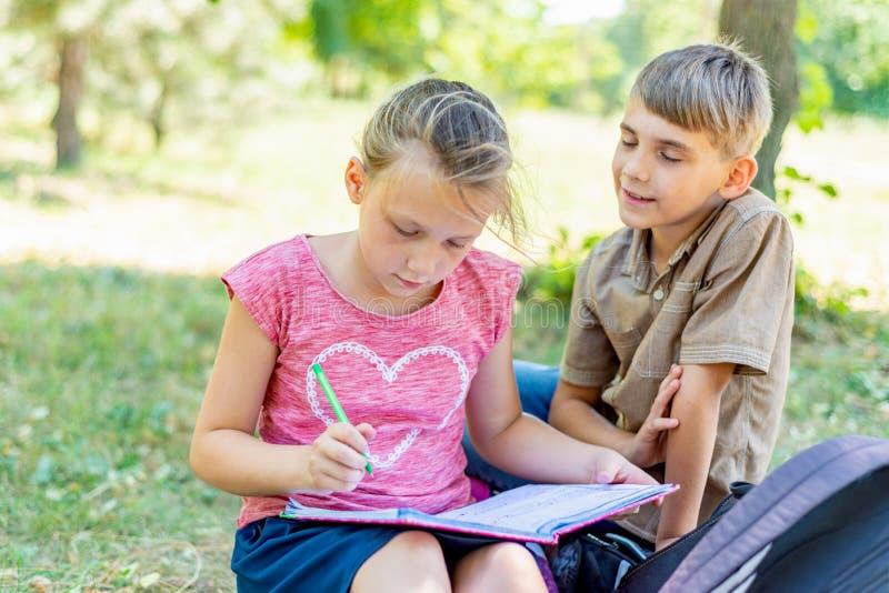 De jongen en het meisje zijn bezig geweest met onderwijs, schrijft het meisje in een notitieboekje, en de jongen vertelt haar stock fotografie