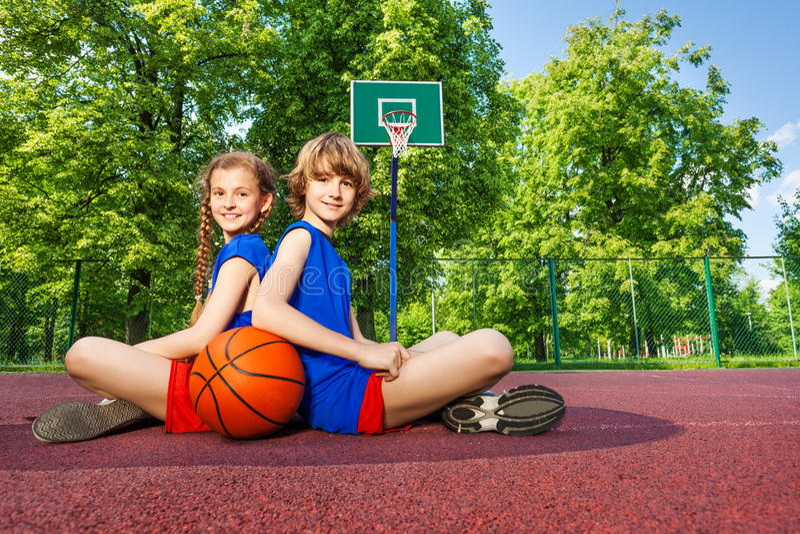 De jongen en het meisje zitten met ruggen dicht op speelplaats royalty-vrije stock foto