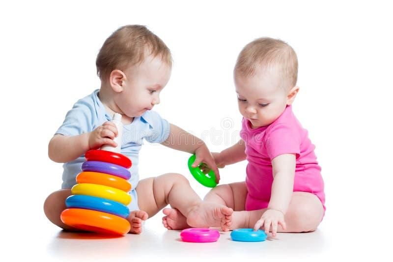De jongen en het meisjesspelspeelgoed van jonge geitjes samen stock afbeeldingen
