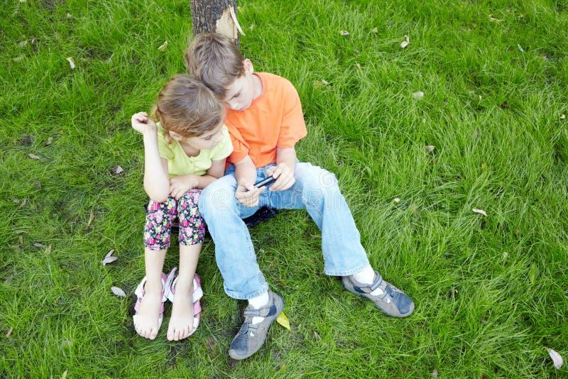 De jongen en zijn zuster zitten en bekijken het scherm van telefoon royalty-vrije stock afbeelding