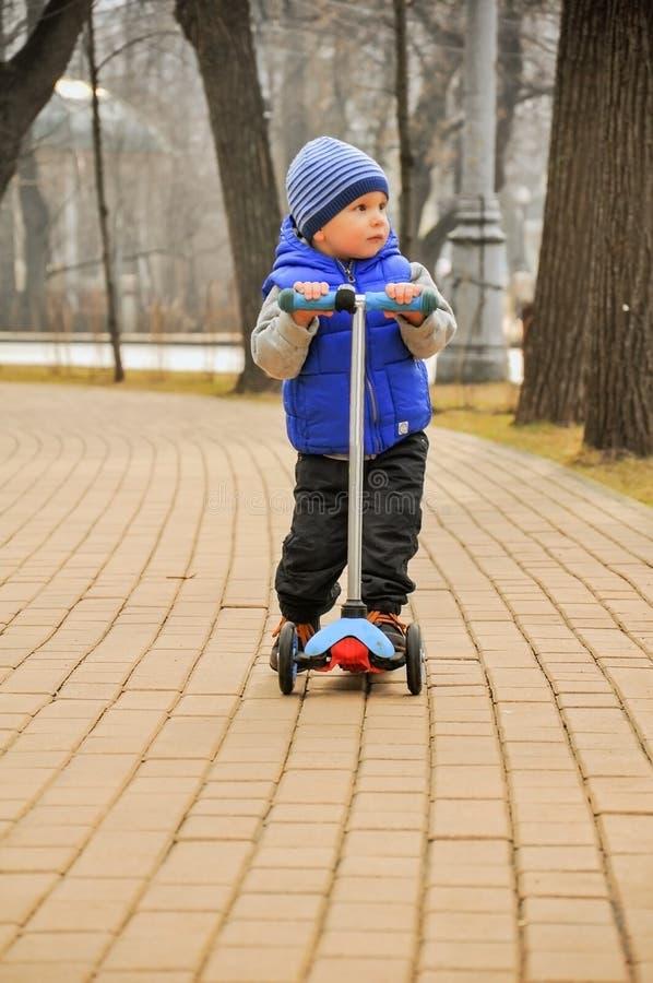 De jongen gaat op de autoped op een weg stock afbeelding