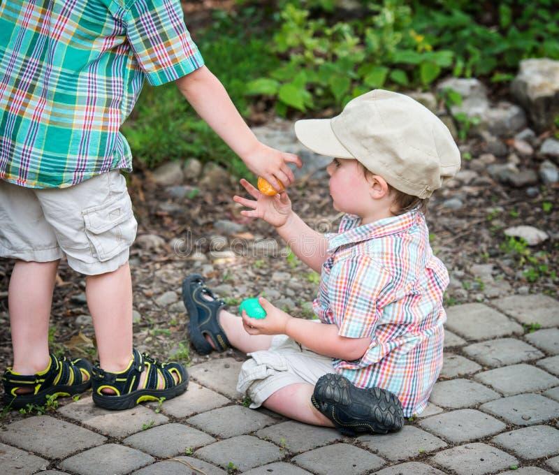De jongen geeft Paasei aan Zijn Kleine Broer royalty-vrije stock fotografie