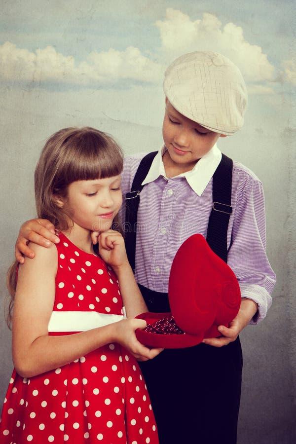 De jongen geeft parels aan het meisje Retro stijl stock fotografie