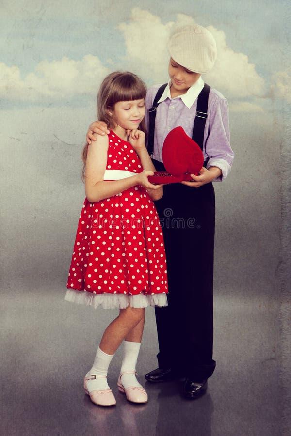 De jongen geeft parels aan het meisje Retro stijl royalty-vrije stock afbeelding