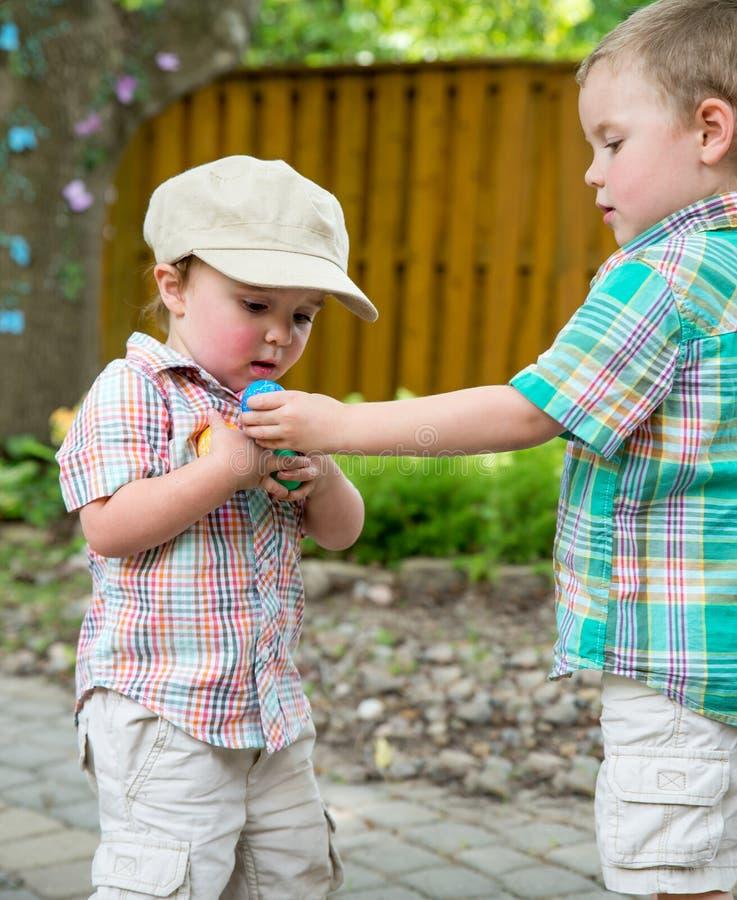 De jongen geeft Zijn Broer een Paasei royalty-vrije stock fotografie