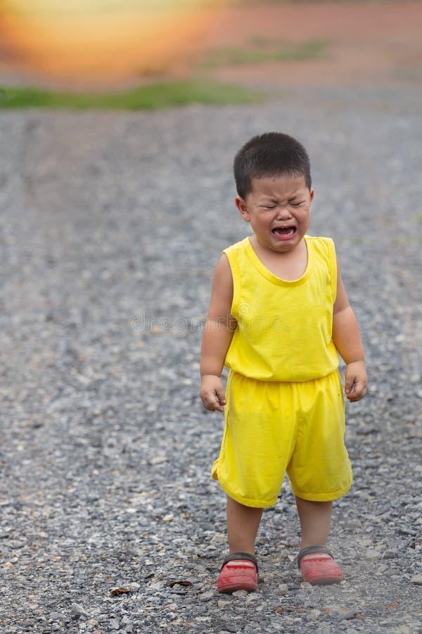 De jongen in gele kleding schreeuwt royalty-vrije stock afbeeldingen