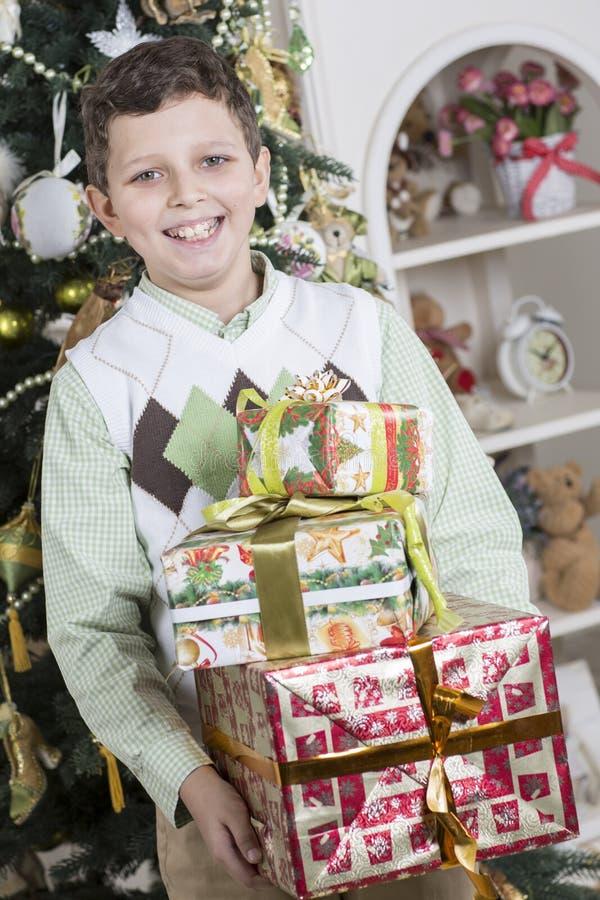 De jongen is gelukkig met vele Kerstmisgiften
