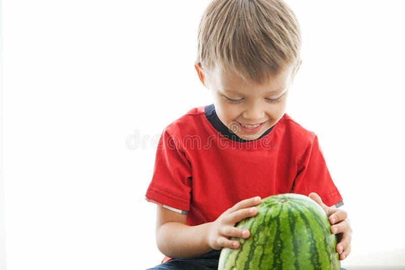 De jongen is gelukkig met de watermeloen stock foto