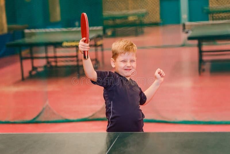 De jongen is gelukkig om in pingpong te winnen stock afbeeldingen