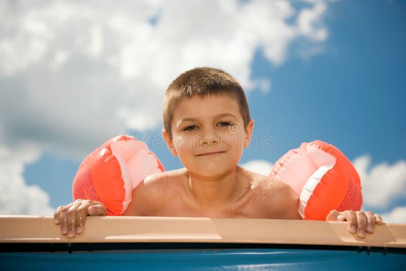 De jongen geniet van in de pool stock afbeelding