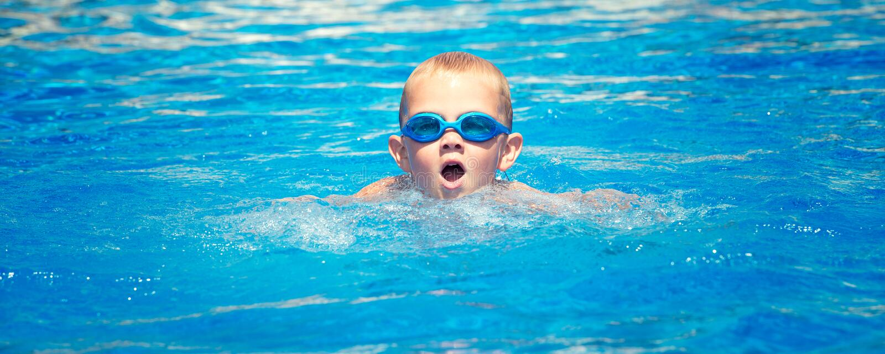 De jongen in glazen voor het zwemmen zwemt in de pool stock afbeeldingen