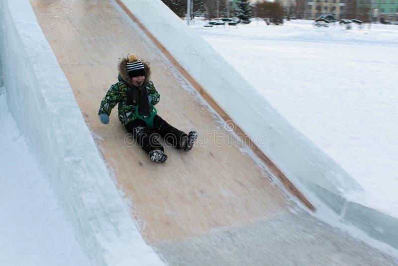 De jongen glijdt op de ijsdia stock afbeelding