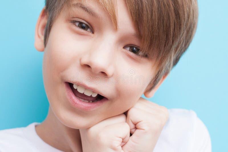 De jongen glimlacht en geraakt Emotieconcept stock fotografie