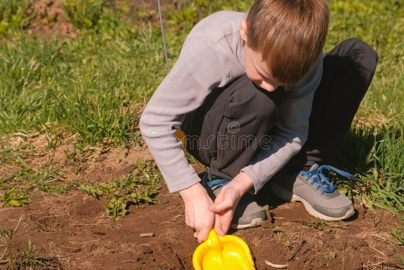 De jongen graaft de grond met een gele plastic schop op het gazon dichtbij het huis royalty-vrije stock afbeeldingen