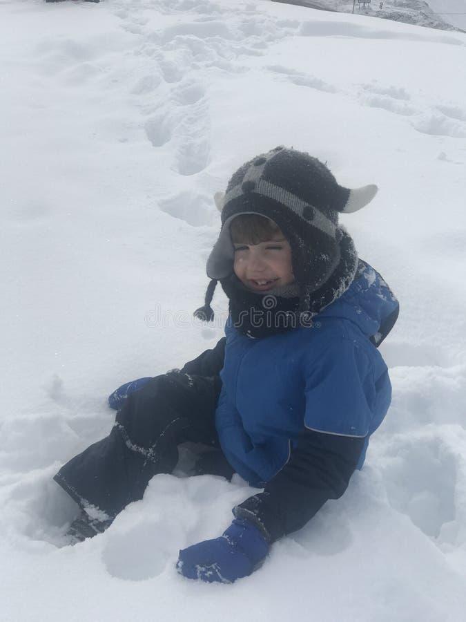 De jongen heeft werkelijk pret na eerst samengekomen de sneeuw stock foto's