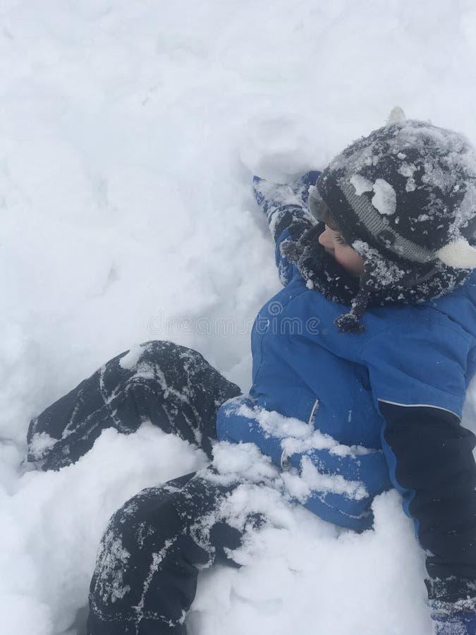 De jongen heeft werkelijk pret na eerst samengekomen de sneeuw stock afbeeldingen