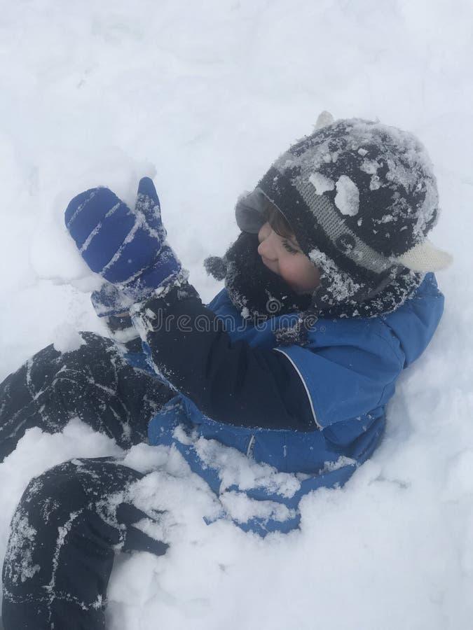 De jongen heeft werkelijk pret na eerst samengekomen de sneeuw stock afbeelding
