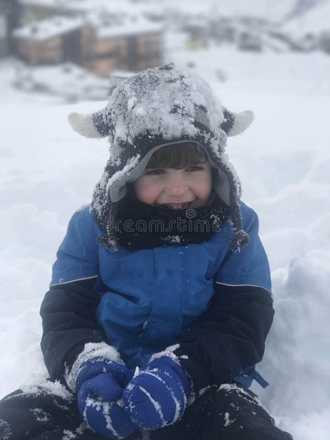 De jongen heeft werkelijk pret na eerst samengekomen de sneeuw royalty-vrije stock fotografie