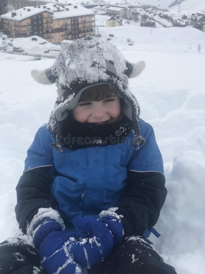 De jongen heeft werkelijk pret na eerst samengekomen de sneeuw royalty-vrije stock afbeelding