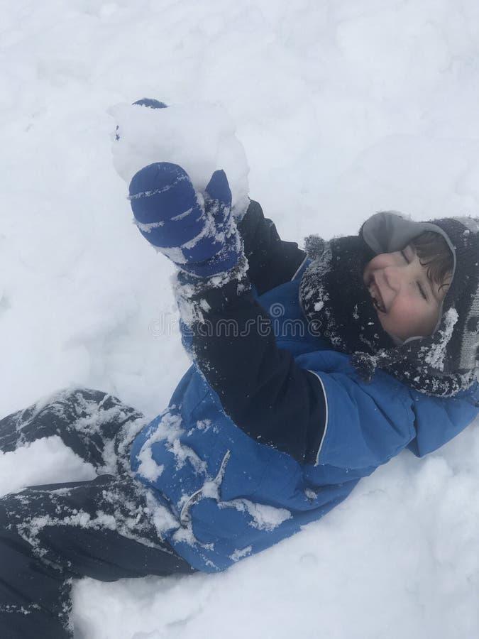 De jongen heeft werkelijk pret na eerst samengekomen de sneeuw royalty-vrije stock afbeeldingen