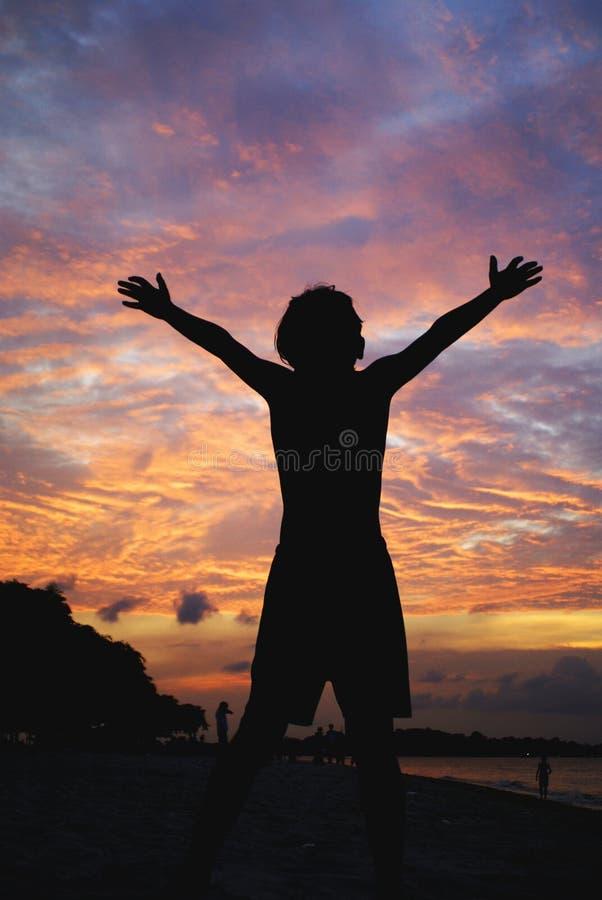 De jongen heft wapens aan zonsondergang op royalty-vrije stock fotografie