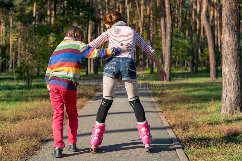 De jongen helpt het meisje aan rolschaats in het park Broer supp stock afbeelding