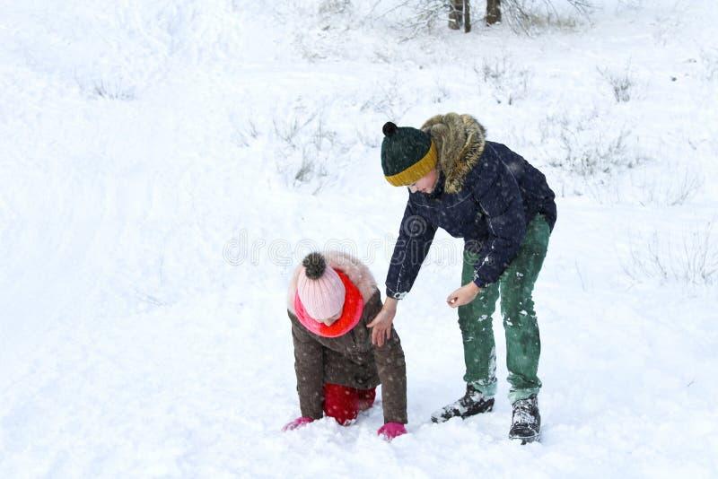 De jongen helpt het meisje om uit de sneeuw en de beweging te beklimmen royalty-vrije stock fotografie