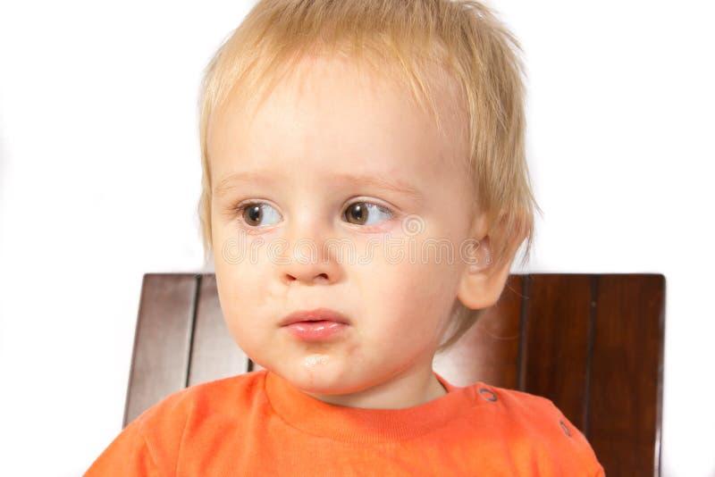 De jongen het blonde in een oranje t-shirt met een droevige blik stock afbeeldingen