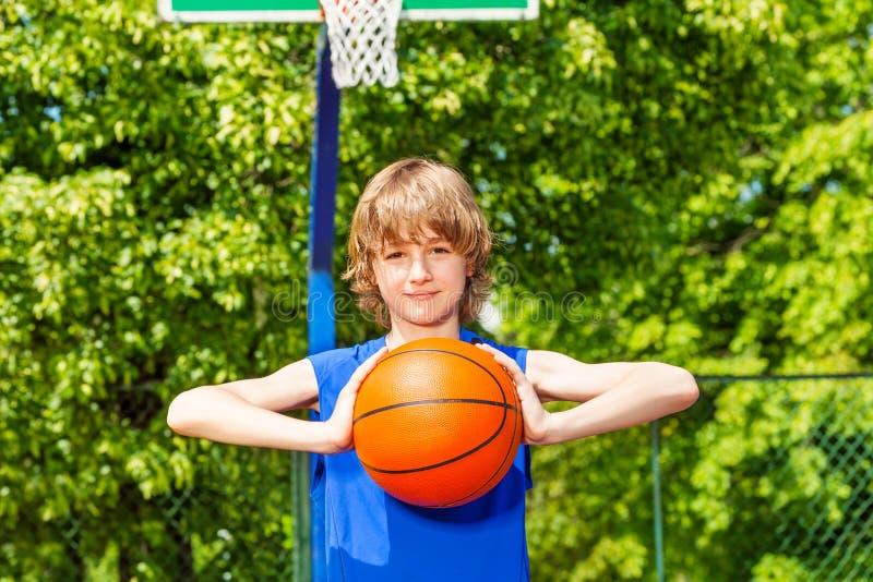 De jongen houdt bal tijdens basketbalspel alleen royalty-vrije stock foto's